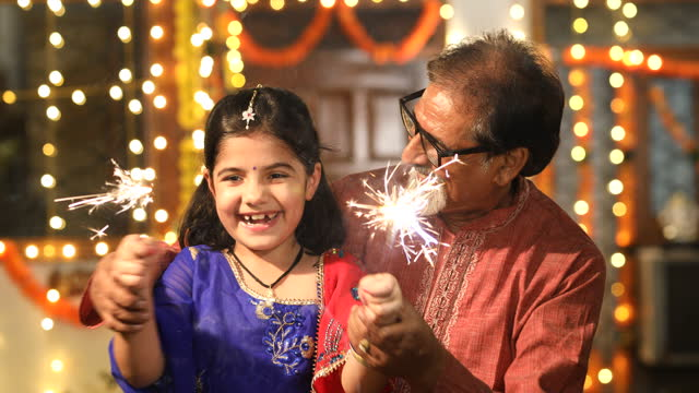 Grandfather and granddaughter playing with crackers during Diwali festival