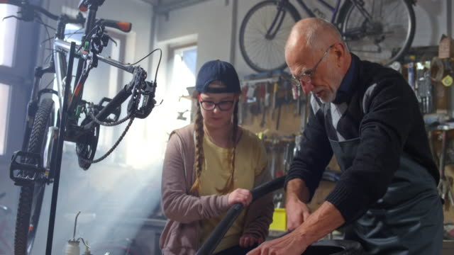 SLO MO Grandfather and granddaughter removing the outer tire of her bike to mend a puncture