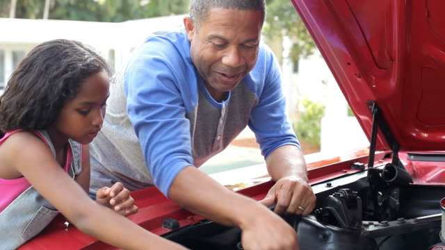 Grandfather And Granddaughter Working On Restored Classic Car Granddaughter helping grandfather as he works on engine of restored classic car.Shot on Sony FS700 at frame rate of 25fps granddaughter stock videos & royalty-free footage