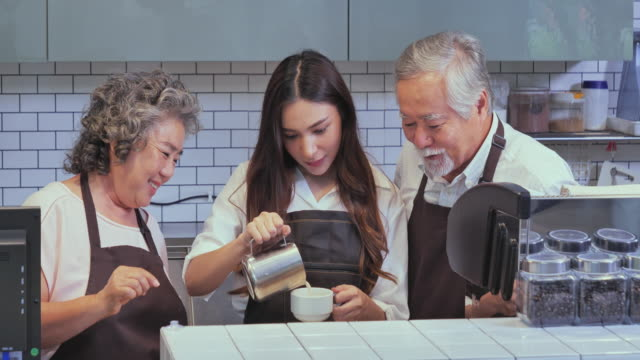 Grandfather and grandmother teaching her granddaughter coffee latte art to be a good barista, lifestyle concept.