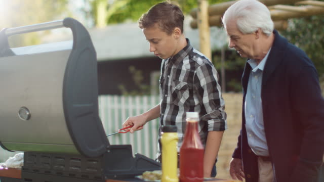 Grandfather and Grandon Are Cooking Burgers on Grill at Bright Summer Day. - vídeo