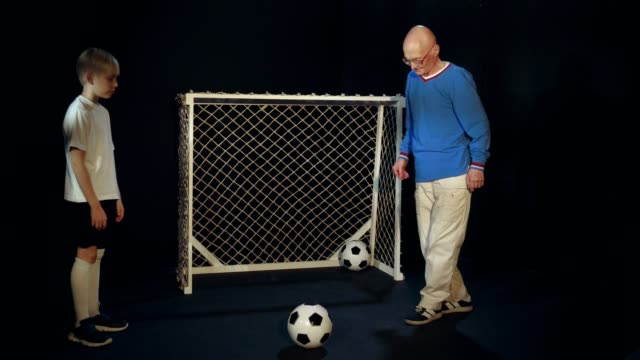 Grandfather And Grandson Are Performing Freestyle Football Juggling video