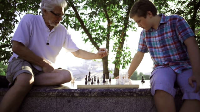 vídeos de stock e filmes b-roll de grandfather and grandson are playing chess in park, slow motion, dolly shot - xadrez