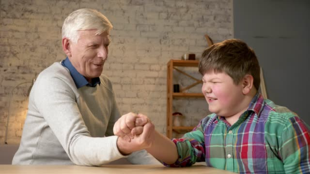 Grandfather and grandson arm wrestle in a cozy room at home. Measuring forces in arm wrestling. Young fat child won. Home comfort, family idyll, cosiness concept, difference of generations, close up. 60 fps video