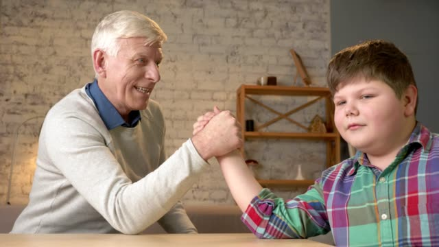 Grandfather and grandson arm wrestle in a cozy room at home. Measuring forces in arm wrestling. Old man won. Home comfort, family idyll, cosiness concept, difference of generations, close up. 60 fps video