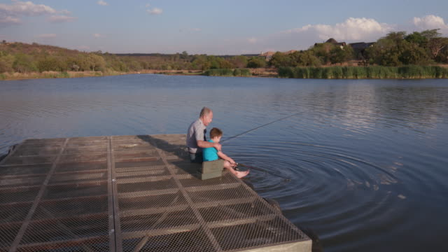 Grandfather and grandson fishing at a small lake video
