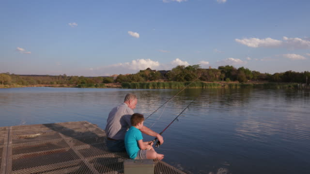 grandfather and grandson fishing at a small lake - grandparents stock videos & royalty-free footage
