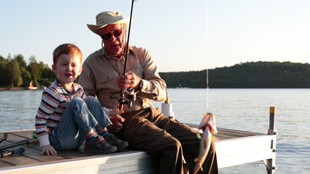 grandfather and grandson fishing at sunset in summer - внук стоковые видео и кадры b-roll