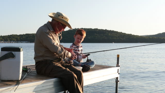 Grandfather and Grandson Fishing At Sunset in Summer A grandfather is teaching his grandson to fish during sunset in summer. They are both sitting on the dock and are concentrated on their activity. It is a beautiful summer day. Across the lake, there is a mountain. hobbies stock videos & royalty-free footage