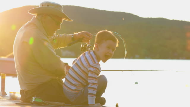 Grandfather and Grandson Fishing At Sunset in Summer A grandfather is teaching his grandson to fish during sunset in summer. They are both sitting on the dock and are concentrated on their activity. It is a beautiful summer day. Across the lake, there is a mountain. catching stock videos & royalty-free footage