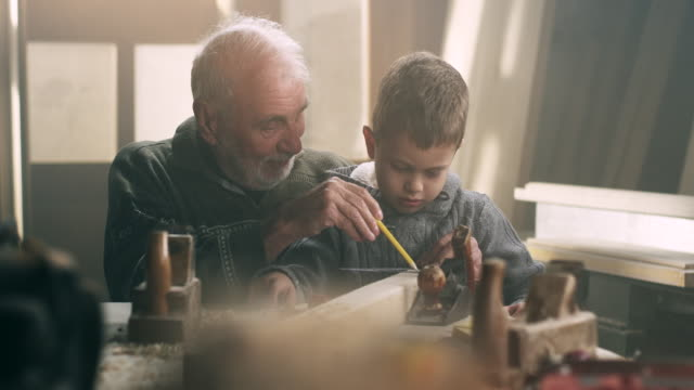 Grandfather and grandson in workshop Grandfather and grandson in workshop recreational pursuit stock videos & royalty-free footage