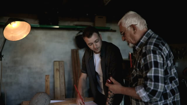 Grandfather and grandson in workshop... video