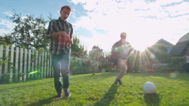 Grandfather and Grandson Play Football in the Backyard. video