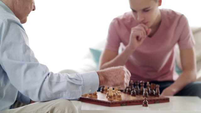 Grandfather and grandson playing chess at home