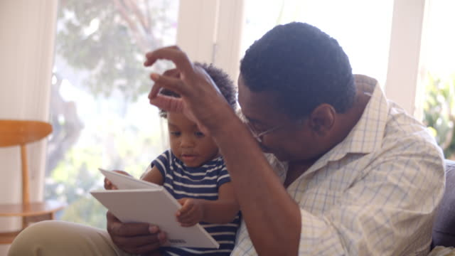 Grandfather And Grandson Reading Book At Home Together video