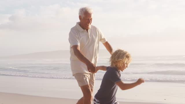 Avô e neto correndo ao longo da praia em câmera lenta - vídeo