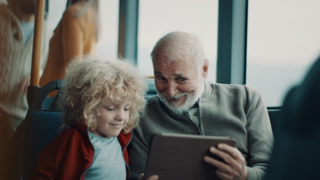 Grandfather and grandson using tablet while riding on the bus together