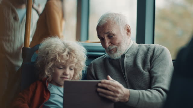 Grandfather and grandson using tablet while riding on the bus together video