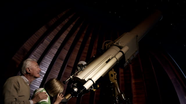 nonno e nipote con telescopio - astronomia video stock e b–roll