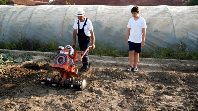 Grandfather and grandson working on a mower Grandfather and grandson working on a mower harrow agricultural equipment stock videos & royalty-free footage