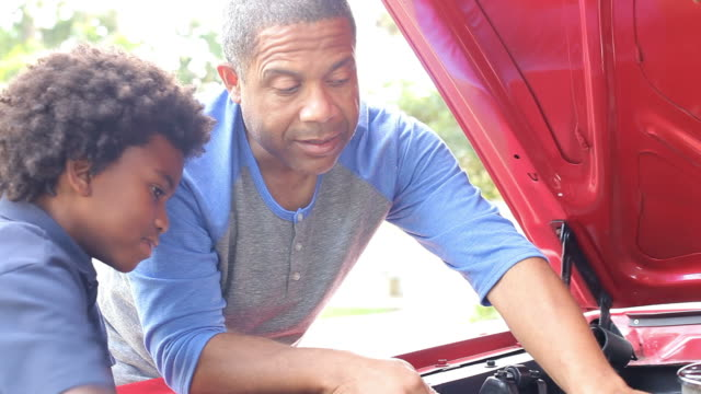 Grandfather And Grandson Working On Restored Classic Car video