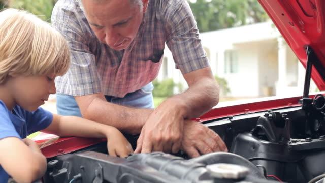 Abuelo y nieto trabajando en el restaurado coche clásico - vídeo