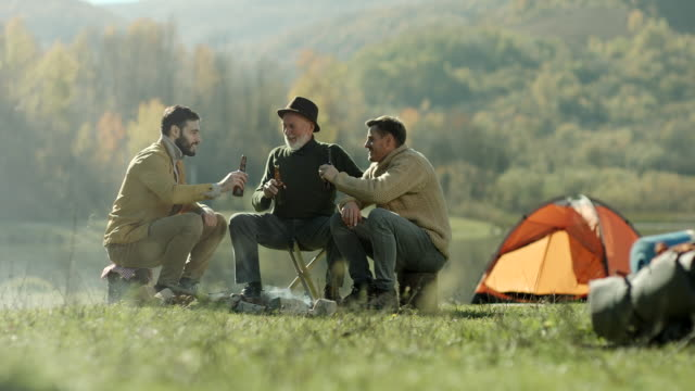Grandfather and grandsons siting by the camp fire talking and drinking beer video