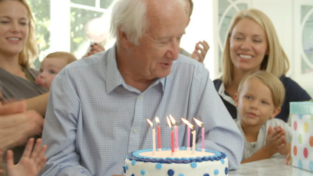 Grandfather Blows Out Candles On Birthday Cake Shot, Slow Motion video
