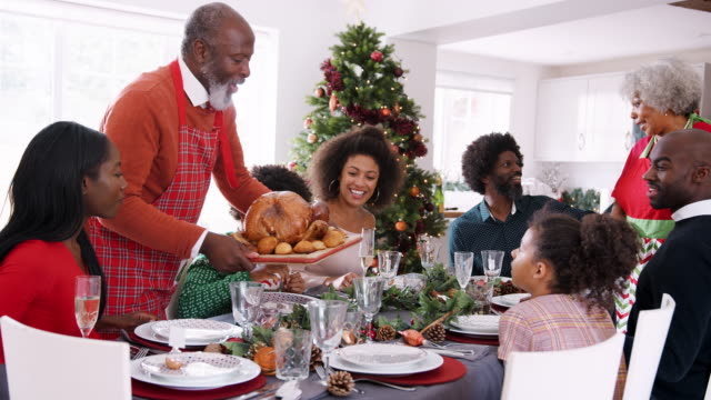 grandfather bringing a roast turkey to the dinner table during a multi generation, mixed race family christmas celebration - cena natale video stock e b–roll