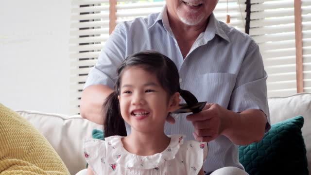 vidéos et rushes de grand-père, brossage des cheveux de petite fille. charmante petite fille sourit tandis que son grand-père est peigner les cheveux de la petite fille. famille heureuse. familles à hong kong - soins capillaires