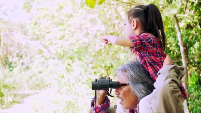 Grandfather carrying  granddaughter on the shoulders and using a long-distance camera.