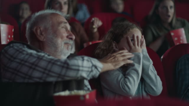 Grandfather consoling scared girl in cinema video