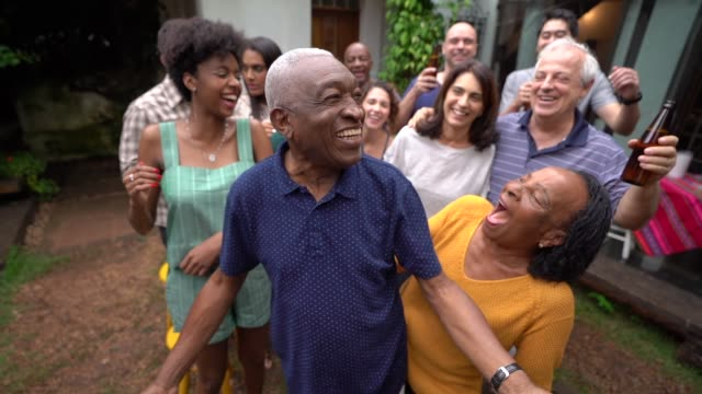 Grandfather dancing with friends/family at barbecue party