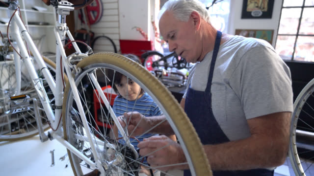 Grandfather doing maintenance to a bicycle at the shop and grandson paying close attention