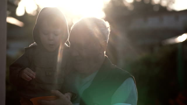 Grandfather holding grandson on his hand. Little boy eating berries, old man looking to the kid and laugh. 4K video