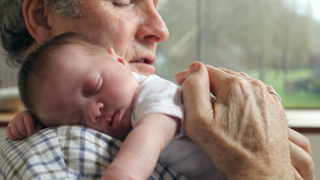 grandfather holding sleeping newborn baby granddaughter - grandparents stock videos & royalty-free footage