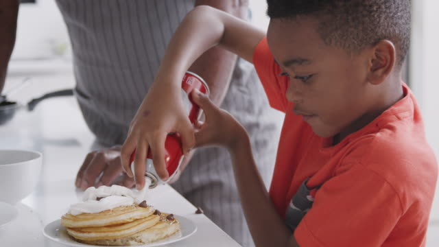 grandfather in kitchen with grandson eating pancakes together - pancake video stock e b–roll