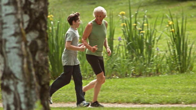 SLO MO TS Grandfather jogging in the park with his grandson Slow motion wide tracking shot of a senior man jogging with his grandson through the park. recreational pursuit stock videos & royalty-free footage