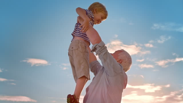 SLO MO Grandfather lifting his grandson into the air in sunshine video