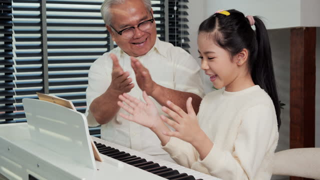Grandfather looking granddaughter playing piano at living room. She was showing play piano to Grandfather with confident.