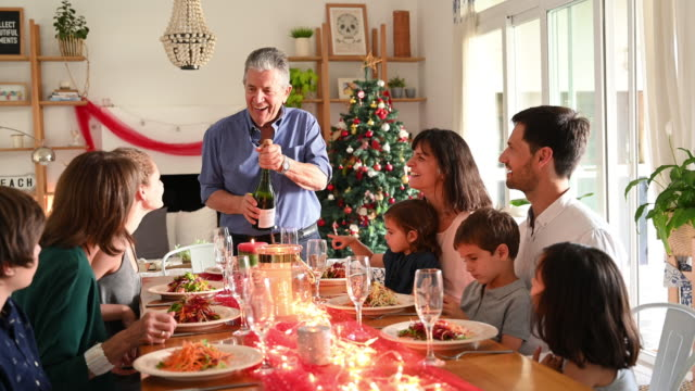 grandfather makes speech and pours champagne at christmas lunch - christmas table video stock e b–roll