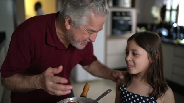 Grandfather making chocolate with granddaughter at home