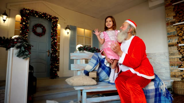 Grandfather playing Santa Claus role for granddaughter video