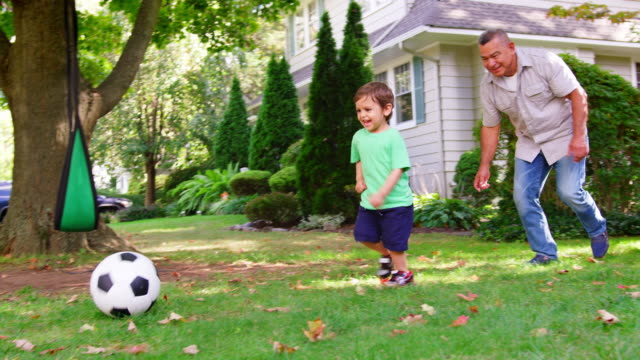 stockvideo's en b-roll-footage met grootvader te voetballen in de tuin met kleinzoon - garden house