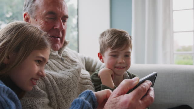 grandfather playing video game with grandchildren on mobile phone at home - внук стоковые видео и кадры b-roll
