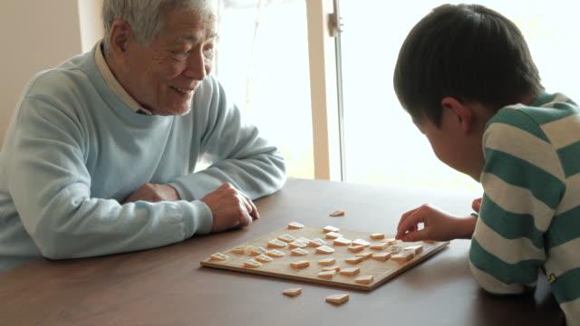 祖父と遊ぶ日本のチェス、孫ご自宅で - シニア点の映像素材/bロール