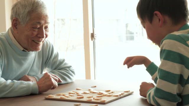 Grandfather playing with a Japanese chess with grandson at home video