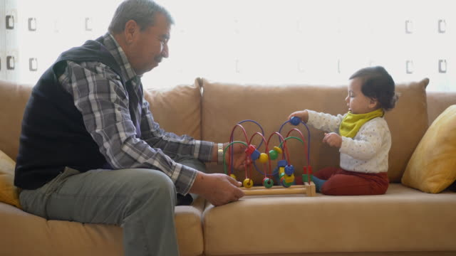 Grandfather playing with little grandson sitting on sofa, plays with a bead roller coaster