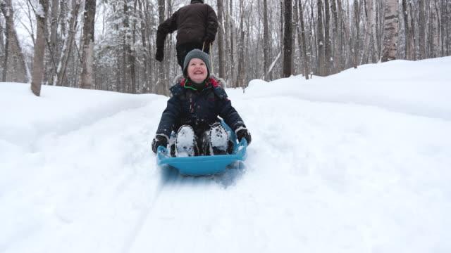 grandfather pulling grandson on sled in winter - slitta video stock e b–roll