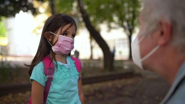 dedesi okul bahçesinde torununa koruyucu yüz maskesi koyarak - sırt çantası stok videoları ve detay görüntü çekimi